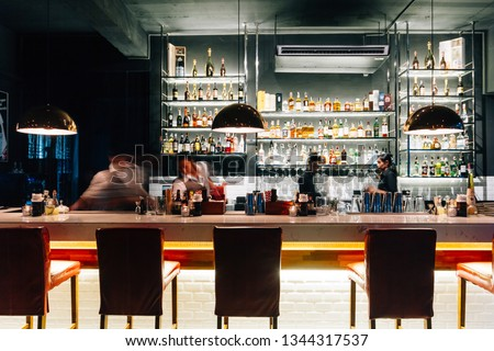 BANGKOK, THAILAND. SEP 5, 2016: Counter bar with many brands of liquor on glowing shelf with moving bartenders in the restaurant. #1344317537