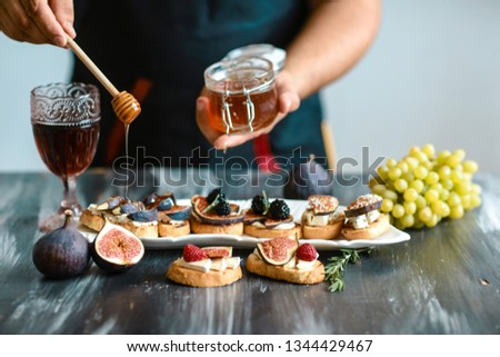 Sandwiches with cheese, fresh figs and honey on rustic wooden board Presentation on wooden table bruschetta with figs, cheese. top view. #1344429467