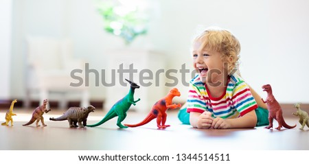 Child playing with colorful toy dinosaurs. Educational toys for kids. Little boy learning fossils and reptiles. Children play with dinosaur toys. Evolution and paleontology game for young kid. #1344514511