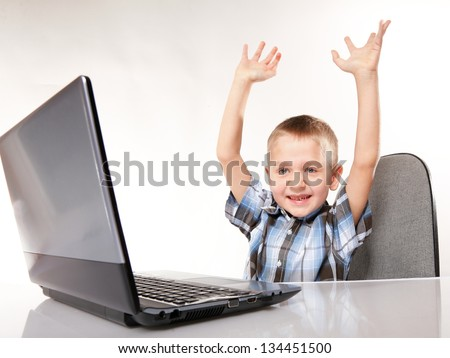 Triumphing child boy with a laptop notebook computer isolated on white background. Computer addiction. #134451500