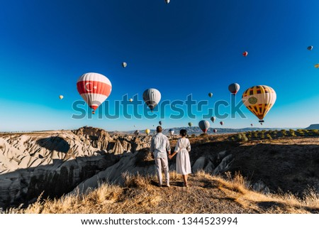 Couple in love among balloons. Loving couple rear view. Couple in love in Cappadocia. Couple in Turkey. Honeymoon in the mountains. Man and woman traveling. Flying on balloons. Wedding. Journey. Love #1344523994