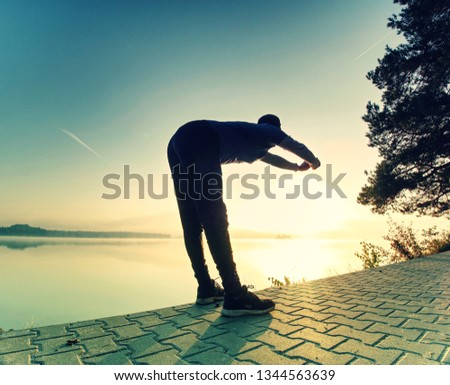 Short break for breath. Silhouette of active man exercising and stretching on the lake beach at sunrise. Healthy lifestyle.  #1344563639