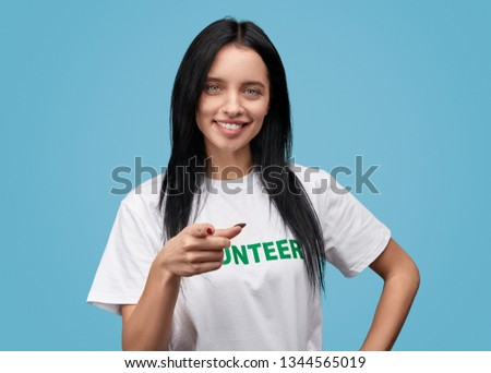 Lovely lady in white T-shirt smiling and pointing at camera while standing on blue background #1344565019