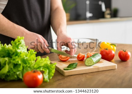 Young trendy man cooking healthy food in the morning #1344623120