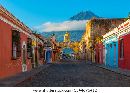 Cityscape of the main street and yellow Santa Catalina arch in the historic city center of Antigua at sunrise with the Agua volcano, Guatemala. #1344676412