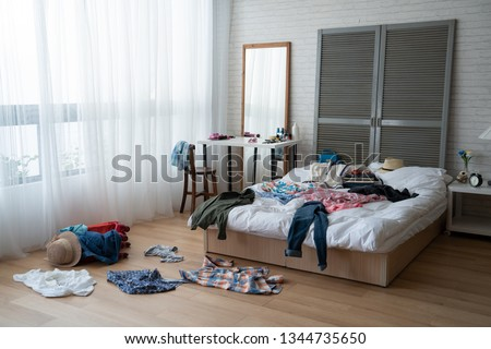 modern bright bedroom with messy clothes scatter on white bed and floor. empty room with nobody in cozy apartment. packing luggage suitcase for summer vacation and spring holidays concept lifestyle. Royalty-Free Stock Photo #1344735650