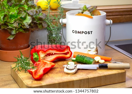 Food waste recycle, kitchen food waste from food preparation collected for recycling in kitchen compost collecting pot container with chopped vegetables with knife on chopping board  #1344757802