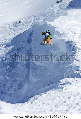 A snowboarder jumping off the ridge #134489492