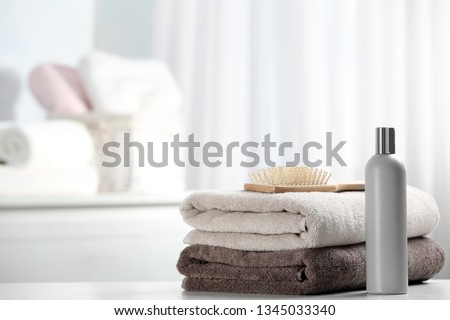 Towels with hair brush and shampoo on table. Space for text Royalty-Free Stock Photo #1345033340