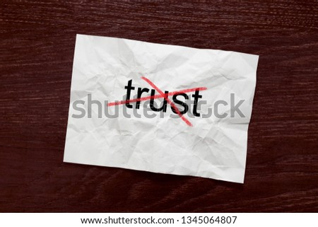 """Striking out the word """"trust"""" on crumpled paper #1345064807"""