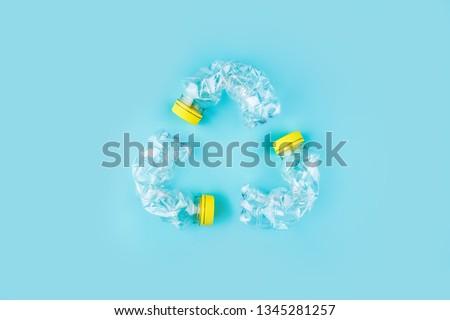 Three crashed plastic bottles on blue background form resycling sign. Plastic utilisation concept. Attractive ecological problem positive poster.  #1345281257