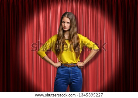 Young angry woman wearing jeans and yellow shirt on red stage curtains background. Digital art. Feelings and emotions. People and objects. #1345395227