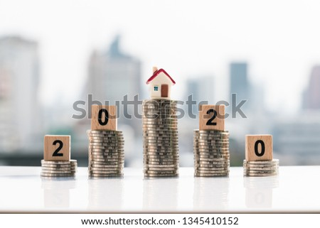 Money, Financial, Business Growth concept. Small house and 2020 wooden blocks on top of coin stack on city backgrounds. #1345410152