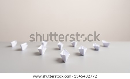 Paper made origami boats placed on an office desk in an arrow shaped position in a conceptual image. #1345432772