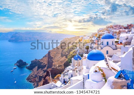 Beautiful Oia town on Santorini island, Greece. Traditional white architecture  and greek orthodox churches with blue domes over the Caldera, Aegean sea. Scenic travel background. #1345474721