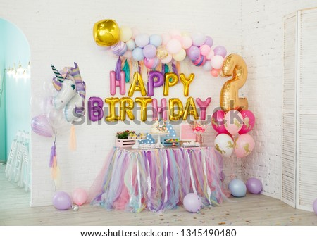 Room decoration for children's birthday with a unicorn. A table with sweets stands on the background of white brick walls: marshmallows, cupcakes, blueberry cake with chocolate cream, garland, cookie