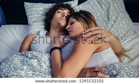 Young couple sleeping embraced in bed at home #1345532102