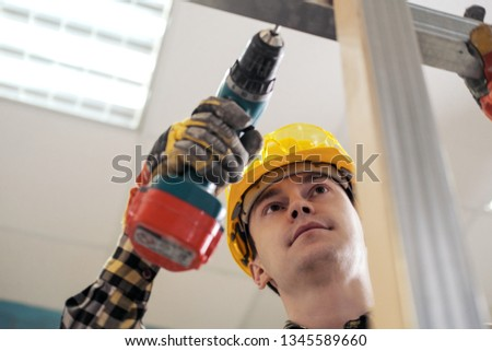 Young male construction worker and repairman working with a screwdriver and metal profile. The concept of the construction of plasterboard walls on a metal frame. #1345589660