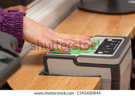 The process of scanning fingerprints during the check at border crossing. Female hand puts fingers to the fingerprint scanner. Identity verification and border control, immigration concept #1345600844