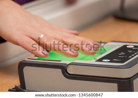 The process of scanning fingerprints during the check at border crossing. Female hand puts fingers to the fingerprint scanner. Identity verification and border control, immigration concept #1345600847