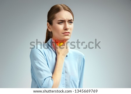 Throat pain. Woman holding her inflamed throat. Photo of american woman in blue shirt on gray background. Medical concept Royalty-Free Stock Photo #1345669769