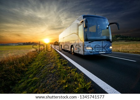 Bus traveling on the asphalt road in rural landscape at sunset                                Royalty-Free Stock Photo #1345741577