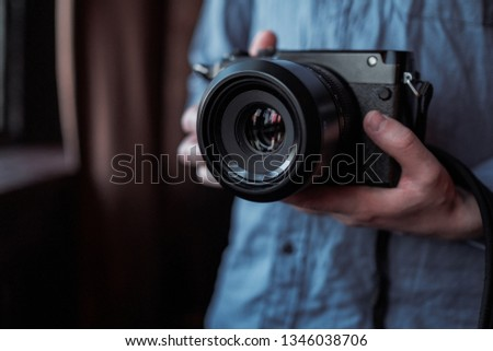 MOSCOW, RUSSIA - 14 MARCH 2019: Fujifilm GFX50s Camera, Fujifilm Mirrorless. Close-up of hand holding camera. Mirrorless camera close up in the hand of a young man on a studio background. #1346038706
