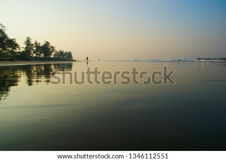 dawn on the tropical shore. reflection of the dawn sky and tropical trees in the water #1346112551