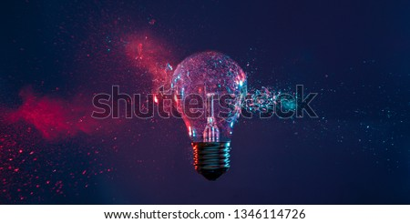 High speed studio photography, moment of the impact of a bullet on a classic electric bulb. Detail of glass explosion, blue and purple lighting. Concept of obsolete energy.