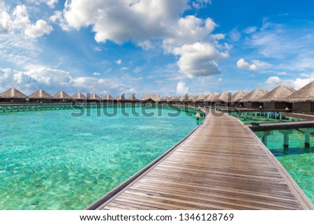 Water Villas (Bungalows) and wooden bridge at Tropical beach in the Maldives at summer day #1346128769
