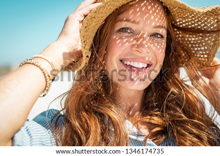 Portrait of beautiful woman wearing straw hat with large brim at beach and looking at camera. Closeup face of attractive smiling girl with freckles and red hair. Happy mature woman enjoying summer. #1346174735