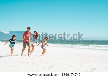 Happy young family running on the beach with copy space. Beautiful mother and laughing father enjoying summer vacation with son and daughter. Smiling parents with two children in casual having fun. #1346174747