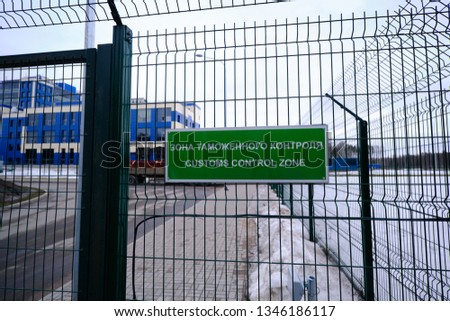 Customs control zone - a sign in Russian and English at the entrance to the vehicle inspection point. The plate is green on the metal grill. Pointer and warning about entering a special area.