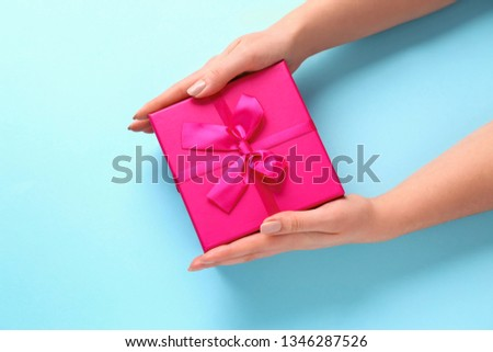 Female hands with gift box on color background #1346287526