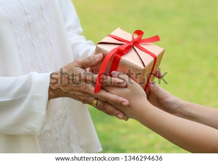 Cropped image of the girl giving a gift to a grandmother on birthday #1346294636