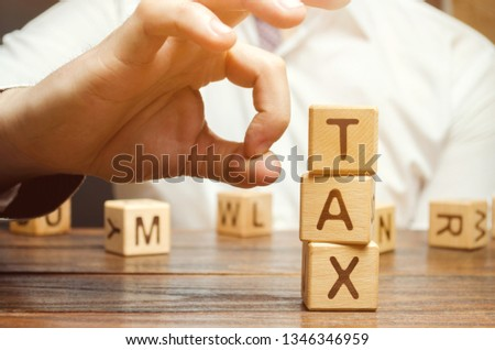 Businessman removes wooden blocks with the word Tax. The concept of reducing the tax burden. Tax avoidance. Costs and expenses of the business. Taxation. Pay off debt. Freedom from illegal taxes #1346346959