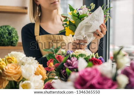 Partial view of florist making bouquet in flower shop #1346365550