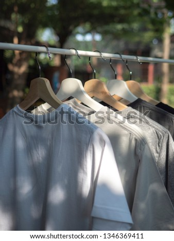 White, grey and black t-shirts on hangers, close up view  #1346369411