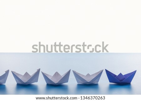 Paper boats on light blue surface on white background #1346370263