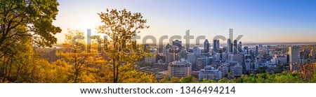 Amazing view of Montreal city at sunrise with colorful blue architecture, green and yellow landscape. Beautiful sky and sun light over Montreal downtown skyline in morning time. Magic Canadian city.