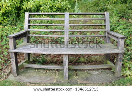Traditional curved wooden park seat on stone paving slabs surrounded by plants with grass in the foreground. #1346512913