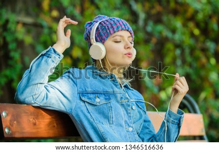 modern technology instead of reading. relax in park. hipster girl with mp3 player. hipster woman in headset. audio book or mp3 player. style and music. listening music in park on mp3. listen to mp3. #1346516636
