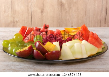 Fruit mix. Peach, grapes, apple, watermelon, melon, raspberry, plum. Pieces of fruit on a plate lie on a white wooden background. Copy space, space for text. #1346576423