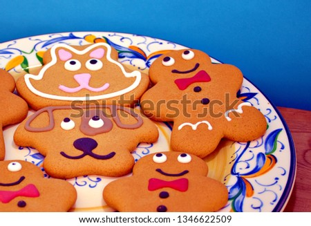 A image of gingerbread figures on a patterned plate with a blue background ,the image is cropped for a different look. #1346622509