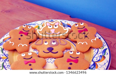 A flat cropped image of gingerbread figures on a patterned plate with a blue background.  #1346623496