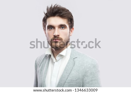 Portrait of handsome bearded serious man with brown hairs and beard in white shirt and casual grey suit standing and looking at camera. indoor studio shot, isolated on light grey background. #1346633009
