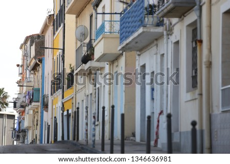 Outdoor view of colored houses facades in the center of sète city, southern France. March, 12, 2019. Narrow street composed of ancient constructions with balconies and windows. Sunny day in the town. #1346636981