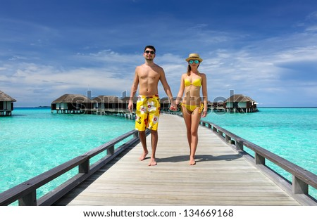 Couple on a tropical beach jetty at Maldives #134669168