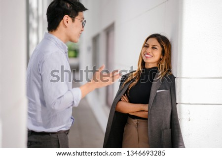 Two young and confident professional Asian business people stand and talk to one another in the city during the day. They are a diverse pair, one a Korean man and the other a Southeast Asian woman. #1346693285