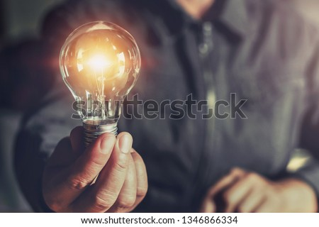 hand holding light bulb. idea concept with innovation and inspiration #1346866334